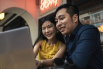 Happy young asian couple using laptop together — Stock Photo