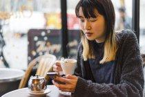Jeune femme asiatique casual attrayante buvant café au café — Photo de stock