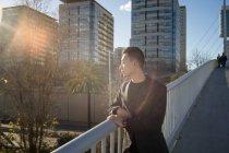Joven asiático hombre buscando fuera en ciudad - foto de stock
