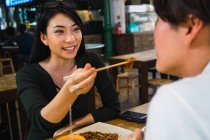 Young asian couple sharing food in street cafe — Stock Photo