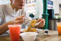 Asiatique homme manger nourriture avec baguettes dans café — Photo de stock