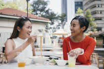 Young asian female friends at food court — Stock Photo