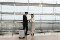 Young asian couple of businesspeople waiting in airport — Stock Photo