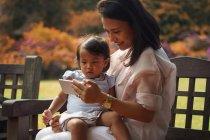 Gira asiática mãe e filha usando smartphone no parque — Fotografia de Stock