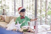Heureux jeune asiatique garçon dans santa chapeau célébrer noël à table — Photo de stock