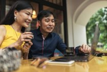 Happy young asian couple using laptop in cafe — Stock Photo