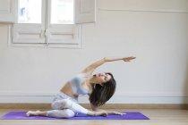 Junge asiatische Frau tun stretching Übungen gegen Wand — Stockfoto