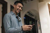 Молодые азиатские человек с помощью смартфона, крупным планом — стоковое фото