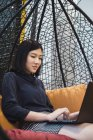 Young asian woman using laptop in creative modern office — Stock Photo