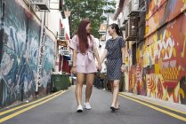 Young asian female friends walking — Stock Photo