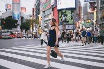 Jeune femme traversant les rues de Tokyo, Japon — Photo de stock