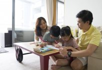 Family bonding at home over a colouring activity for the children — Stock Photo