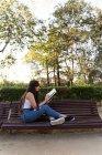 Eurasiática joven leyendo un libro sobre un banco en el Parque - foto de stock