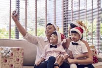 Happy asian family celebrating christmas together and taking selfie at home — Stock Photo