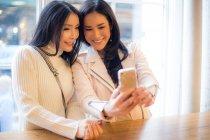 Sorridentes jovens mulheres no café — Fotografia de Stock