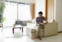 Зрілі азіатських випадковий людина, читаючи книгу в домашніх умовах — стокове фото