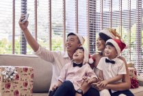 Happy young asian family celebrating christmas together and taking selfie — Stock Photo