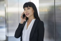 Young attractive asian businesswoman using smartphone in modern office — Stock Photo