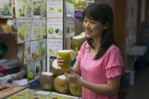 Happy asian woman with fresh juice in chinatown cafe — Stock Photo