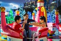 Feliz asiático irmãos passando tempo juntos no parque de diversões no Natal — Fotografia de Stock