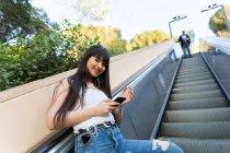 Eurasian woman listening to music on escalator — Stock Photo