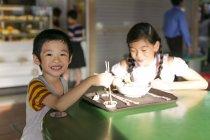 Deux heureux jeunes asiatiques enfants manger au café — Photo de stock