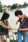 Две молодые женщины наблюдают за рыбой в пруду — стоковое фото
