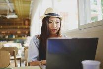 Красивая молодая азиатка с ноутбуком в кафе — стоковое фото