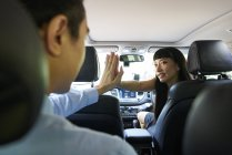Cheerful woman driver giving her passenger a Hi-five — Stock Photo