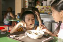 Two happy young asian children eating in cafe — Stock Photo