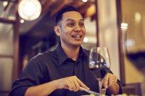 Jeune asiatique beau homme dans café avec vin — Photo de stock