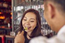 Joven atractivo asiático pareja teniendo fecha en café, hombre alimentación mujer - foto de stock