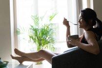 Jovem chinês tomando café da manhã no sofá em casa — Fotografia de Stock
