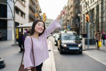 Young Chinese tourist woman flagging a cab in barcelona — Stock Photo
