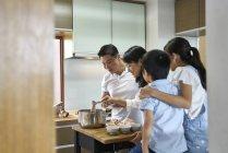 Feliz asiático familia preparación comida juntos en casa - foto de stock