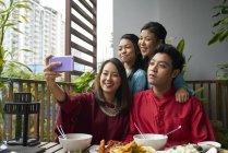 Familia asiática joven celebrar Hari Raya en Singapur y tomar selfie - foto de stock