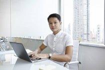 Giovane uomo d'affari asiatico al lavoro in ufficio moderno — Foto stock