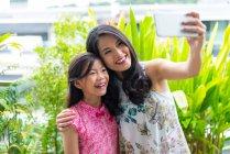 Glücklich asiatische Frau und Tochter Selfie auf Smartphone — Stockfoto