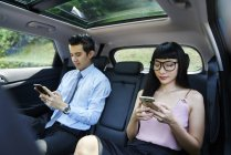 Young asian attractive couple on mobiles in the car — Stock Photo