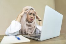 Young asian muslim woman using laptop indoors — Stock Photo