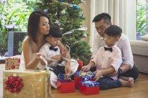 Famiglia di quattro persone si siede sul pavimento e apre i regali di Natale — Foto stock