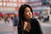 Giovane e bella donna cinese in Plaza Mayor di Madrid, Spagna, con indosso una giacca di pelle — Foto stock