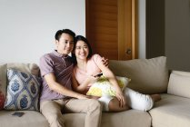 Young casual asian couple watching tv at home — Stock Photo