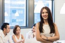 Junge asiatische Kollegen arbeiten zusammen, Frau posiert vor der Kamera im modernen Büro — Stockfoto