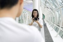 Young attractive asian couple together taking photo on camera — Stock Photo