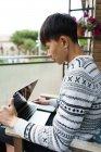 Junge erwachsene asiatische Mann mit Laptop zu Hause — Stockfoto