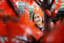 Feliz bela mulher asiática retrato através de ramos de árvore de outono — Fotografia de Stock