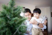 Feliz asiático familia celebrando Navidad juntos en casa, padre e hijo decorando abeto - foto de stock