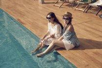 Привлекательные молодые азиатские женщины, отдыхающие у бассейна — стоковое фото