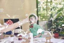 Mãe alimentando filhinho no Natal — Fotografia de Stock